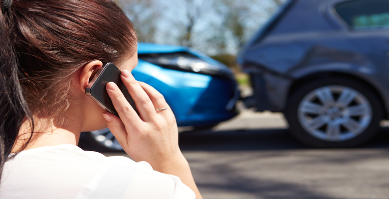 Lady making a phone call following a car accident